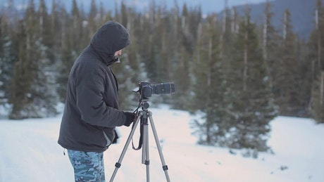 Photographer and his tripod camera in a snowy forest