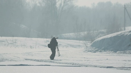 Photographer carring a tripod in the snow