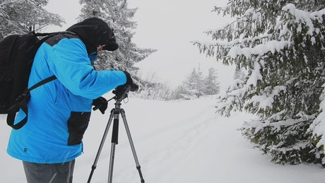 Photographer in a winter forest with his camera