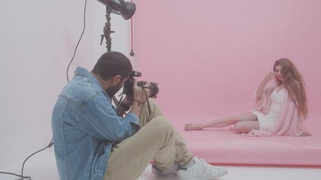 Photographer portraying a young woman on a pink background