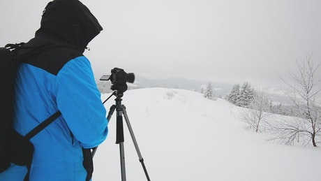 Photographer taking photos while snowing in the forest