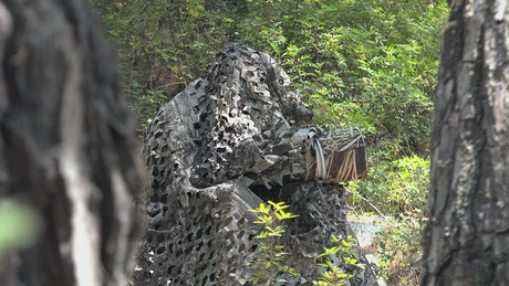Photographer wearing camouflage in the woods