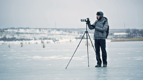 Photographer working in a winter forest