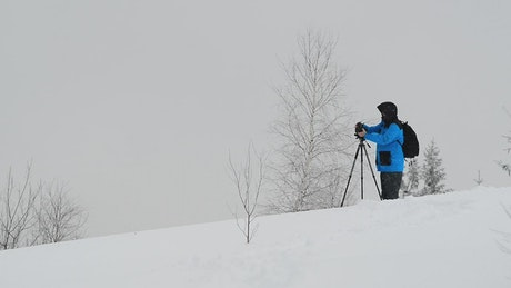 Photographer working while snowing on the mountain