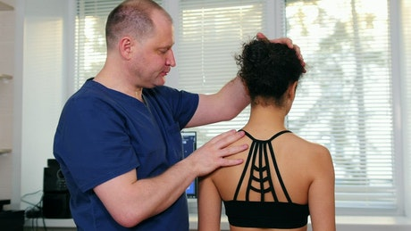 Physiotherapist moving the neck of a female patient