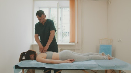 Physiotherapist working on a woman's back pain