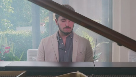 Pianist playing a grand piano in a take to his face