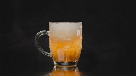 Picking up a small beer mug on a dark background