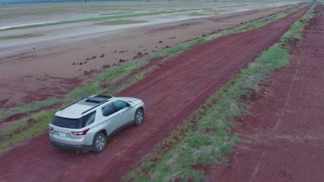 Pickup truck traveling through a desert in an aerial shot