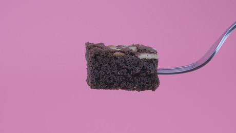 Piece of brownie on a fork on a pink background