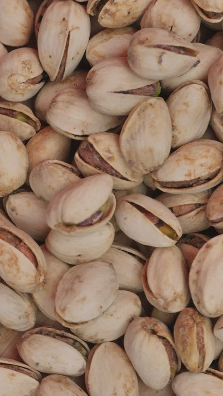 Piled up pistachios spinning seen up close