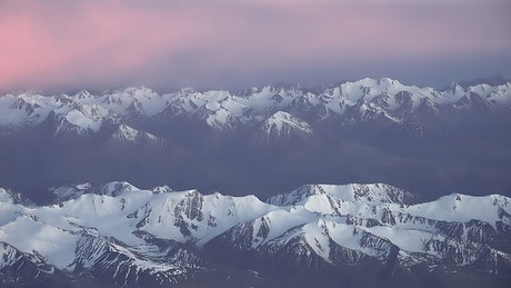 Pink clouds over a snowy mountain range