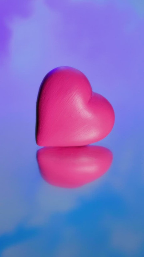 Pink heart on a mirror with the sky and clouds in the background