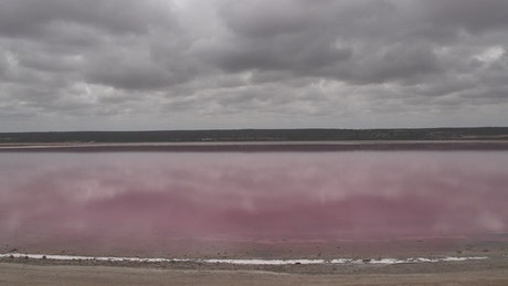 Pink lake under a cloudy sky