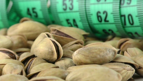 Pistachios and a tape measure, spinning close up