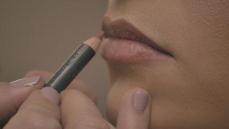 Pitting make up to a woman's lips, close shot