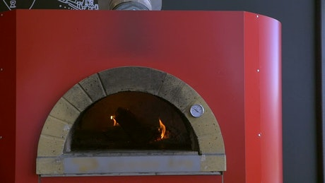 Placing a pizza in a red oven