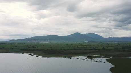 Plain with a lake, trees, grass and hills in the distance
