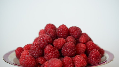 Plate with many raspberries rotating