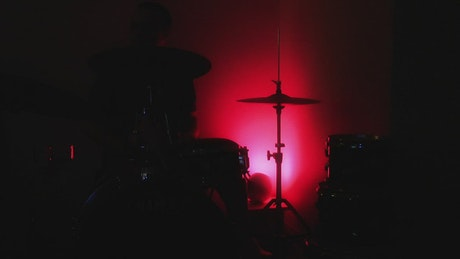 Playing drums in the dark under colored light