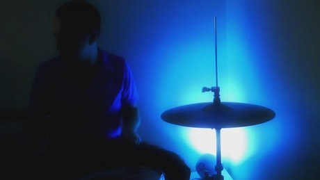 Playing drums in the dark with a lamp colors