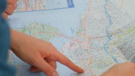 Pointing to a map of a city with his hands