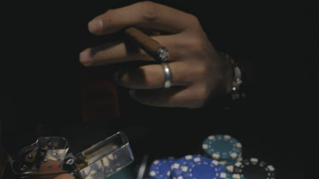 Poker player lighting a cigar
