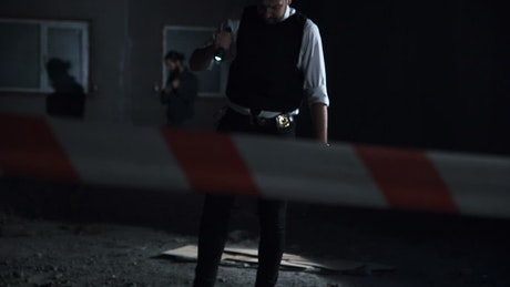 Police man walking on a crime scene