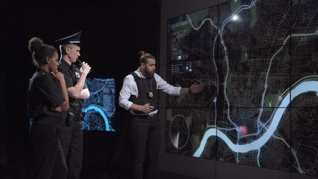 Police officers watching an alert on a map