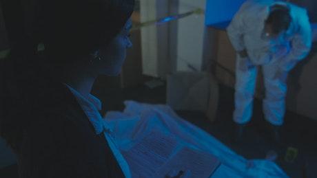 Police woman interrogating the coroner at a crime scene