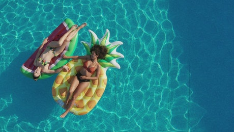 Pool with two girls lying on floats
