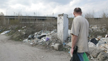 Poor man carrying trash bags