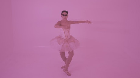 Portrait of a ballerina spinning with pink background