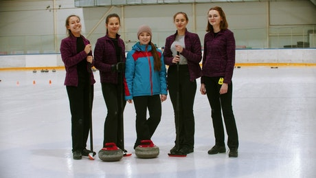 Portrait of a curling team on an ice rink