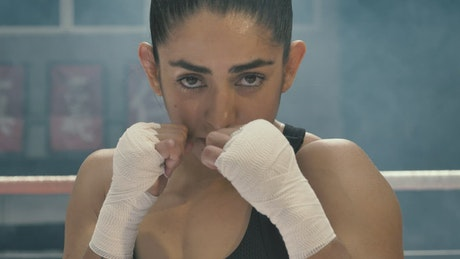 Portrait of a female boxer training on the ring