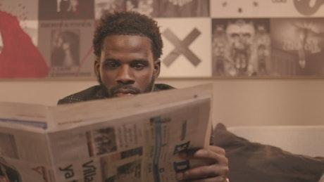 Portrait of a man leafing through a newspaper