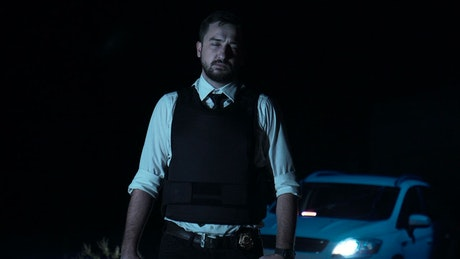 Portrait of a police officer with a vest and with gun