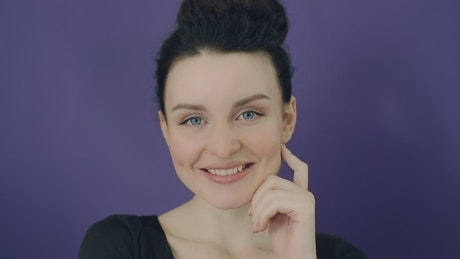 Portrait of a smiling woman with purple background