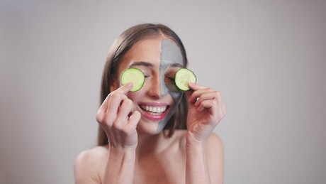 Portrait of a smiling woman with skin mask