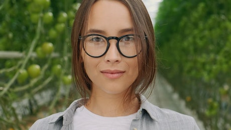 Portrait of an agricultural woman with glasses in a greenhouse