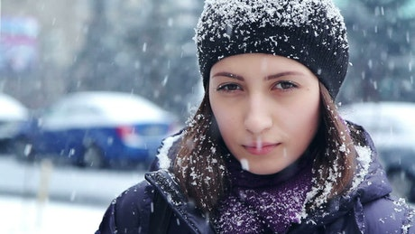 Portrait of woman outdoors while snowing