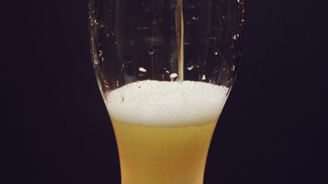 Pouring a cold beer slowly into a glass