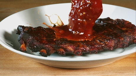 Pouring barbecue sauce on ribs