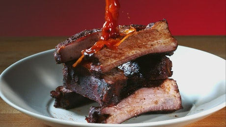Pouring barbecue sauce to ribs on the plate