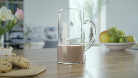 Pouring chocolate milk on the jar