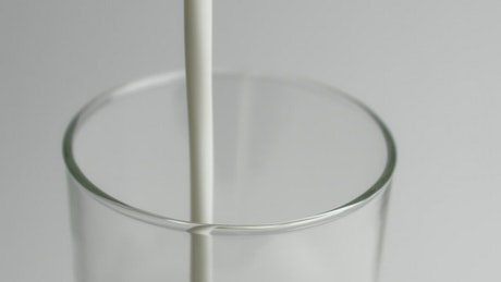 Pouring milk in a glass close up