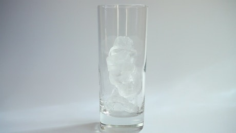 Pouring milk into a glass with ice on a white background