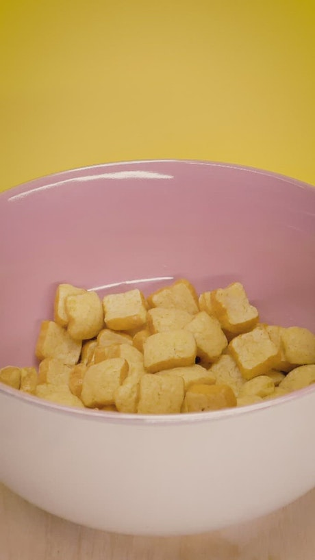 Pouring milk into a pink bowl with cereal