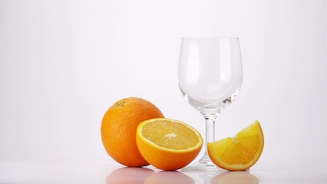 Pouring orange juice into a glass, white background