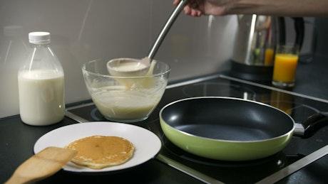 Pouring pancake mix into a pan